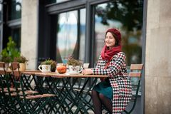 Fashion portrait of woman sitting in street cafe of Budapest. Fashion portrait of young woman sitting at the table in street cafe of Budapest. Woman looking into Royalty Free Stock Image