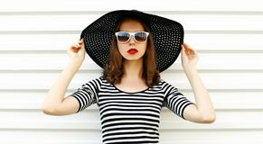 Fashion portrait young woman in summer straw hat posing on white wall stock photo
