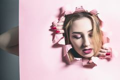 Fashion portrait of a young woman tearing a hole in pink cardboard paper, face of a girl with makeup, creative concept freedom of. Beauty, fashion, cosmetics stock photo