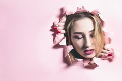 Fashion portrait of a young woman tearing a hole in pink cardboard paper, face of a girl with makeup, creative concept freedom in. Fashion, youth lifestyle stock photo