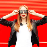 Fashion portrait young woman wearing a rock black jacket and sunglasses over red Stock Photo