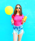 Fashion portrait young woman wearing a t-shirt, denim shorts holds fruit juice cup with yellow air balloon over colorful blue Stock Photos