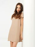 Fashion pose young woman short dress wall Stock Images