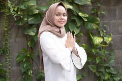 Fashion potrait of young asian female model wearing hijab with hand gesture. Fashion potrait of young model wearing hijab with hand gesture at outdoor area stock photo
