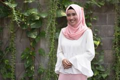 Fashion potrait of young model wearing hijab. Smile at camera in outdoor area royalty free stock image