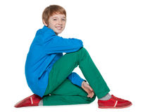 Fashion preteen boy sits. A fashion preteen boy sits on the white background Stock Photography