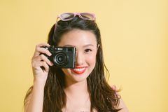 Fashion pretty asian woman with retro camera in hands. royalty free stock photos