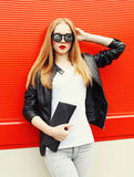 Fashion pretty blonde woman wearing a rock black jacket, sunglasses and handbag clutch over red. Background Stock Image