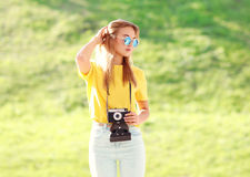 Fashion pretty blonde woman wearing a sunglasses with camera Stock Photo