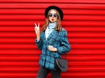 Fashion pretty cool girl blowing red lips making kiss wearing black hat coat jacket handbag over colorful red Royalty Free Stock Photos