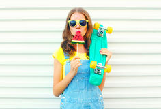 Fashion pretty cool girl eating a slice of watermelon ice cream. Holds a skateboard on a white royalty free stock photos