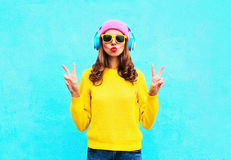 Fashion pretty cool girl in headphones listening to music wearing colorful pink hat yellow sunglasses and sweater over blue. Background Royalty Free Stock Images