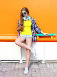 Fashion pretty cool girl with headphones and skateboard using smartphone in city over colorful orange Royalty Free Stock Images