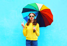 Fashion pretty cool girl listens to music in headphones with colorful umbrella in autumn day over colorful blue background Stock Photo