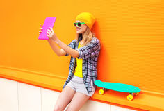 Fashion pretty cool girl makes self portrait on tablet pc over orange colorful Royalty Free Stock Image