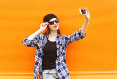 Fashion pretty cool girl makes selfie portrait on smartphone over colorful orange. Background stock photography