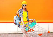 Fashion pretty cool girl with shopping trolley cart and skateboard over colorful Royalty Free Stock Images