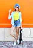 Fashion pretty cool girl with skateboard listens to music over colorful orange Stock Photo