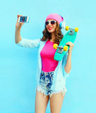 Fashion pretty cool girl with skateboard makes self portrait on smartphone over blue Stock Photos