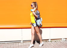 Fashion pretty cool girl in sunglasses with backpack walking in city Stock Image