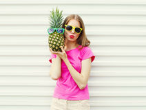 Fashion pretty cool girl in sunglasses with pineapple over white Royalty Free Stock Image