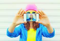 Fashion pretty cool girl taking photo self portrait on smartphone over white background wearing a colorful clothes and sunglasses Royalty Free Stock Image