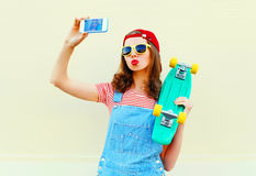 Fashion pretty cool girl is taking picture self portrait on a smartphone over white. Background Stock Images