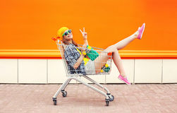Fashion pretty cool girl in trolley cart having fun over colorful orange. Background Stock Photos