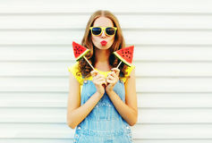 Fashion pretty cool girl with a two slice of watermelon ice cream blowing her lips. Over a white background royalty free stock photography