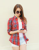 Fashion pretty cool girl using smartphone in city Stock Photography