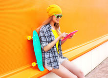 Fashion pretty cool girl using tablet pc with skateboard over colorful orange Royalty Free Stock Photos
