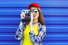 Fashion pretty cool girl wearing a colorful clothes with retro camera shooting Royalty Free Stock Image