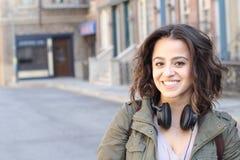 Fashion pretty cool girl wearing headphones having fun over urban background Royalty Free Stock Image