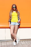 Fashion pretty cool girl wearing a sunglasses and shorts in city over colorful stock images