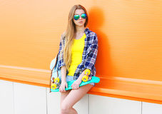 Fashion pretty cool girl wearing a sunglasses with skateboard over colorful Royalty Free Stock Photo