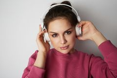 Fashion pretty cool girl in white headphones listening to music wearing colorful pink hoody over white background. Fashion pretty cool girl in white headphones stock image