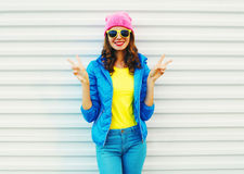Fashion pretty cool smiling girl in colorful clothes having fun over white background wearing a pink hat yellow sunglasses royalty free stock photo