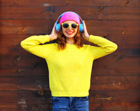 Fashion pretty cool smiling girl enjoying listening to music in headphones wearing colorful pink hat yellow knitted sweater Stock Photo
