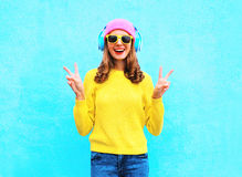 Fashion pretty cool smiling girl in headphones listening to music wearing a colorful pink hat yellow sunglasses and sweater. Over blue background Royalty Free Stock Image