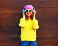 Fashion pretty cool smiling girl listening to music in headphones wearing a colorful pink hat yellow knitted sweater Royalty Free Stock Images