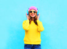 Fashion pretty cool smiling girl listening to music in headphones wearing colorful pink hat, yellow sunglasses and sweater Royalty Free Stock Photo