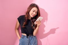 Fashion pretty cool smiling girl, relaxing, listening to music with headphones on a pink background.  stock images