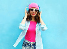 Fashion pretty cool smiling woman listens to music in headphones over colorful blue Royalty Free Stock Images
