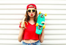 Fashion pretty cool woman with skateboard and banana over white Royalty Free Stock Photo