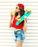 Fashion pretty cool woman with skateboard eating a banana over white Royalty Free Stock Photography