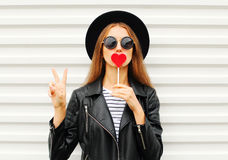Fashion pretty cool young girl with red lollipop heart wearing black hat leather jacket over white urban Royalty Free Stock Image