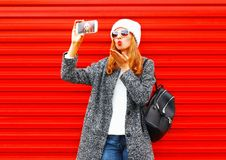Fashion pretty cool young girl takes a picture self portrait on a smartphone on a red. Background Stock Photos