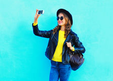 Fashion pretty cool young girl taking photo makes self portrait on smartphone wearing a black rock style clothes over blue Stock Photo