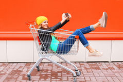 Fashion pretty cool young girl in trolley cart taking picture self portrait on smartphone wearing black jacket hat over colorful Stock Photography