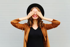 Fashion pretty cool young woman closes eyes cute smiling wearing a vintage elegant hat brown jacket playing having fun. Over grey background Royalty Free Stock Photography